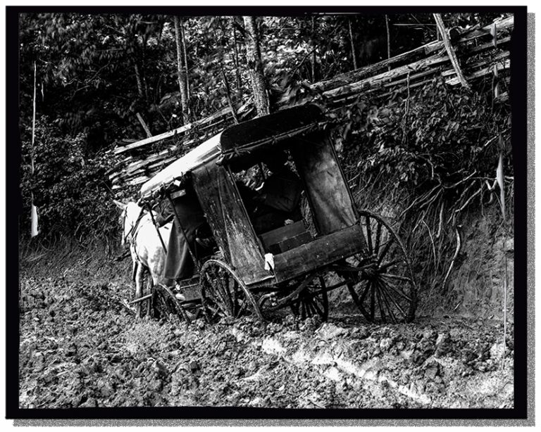 A wagon up to its axle in mud