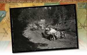 Two Glidden tour automobiles on a muddy road