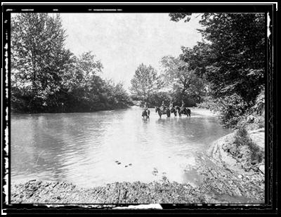 Horses fording a river